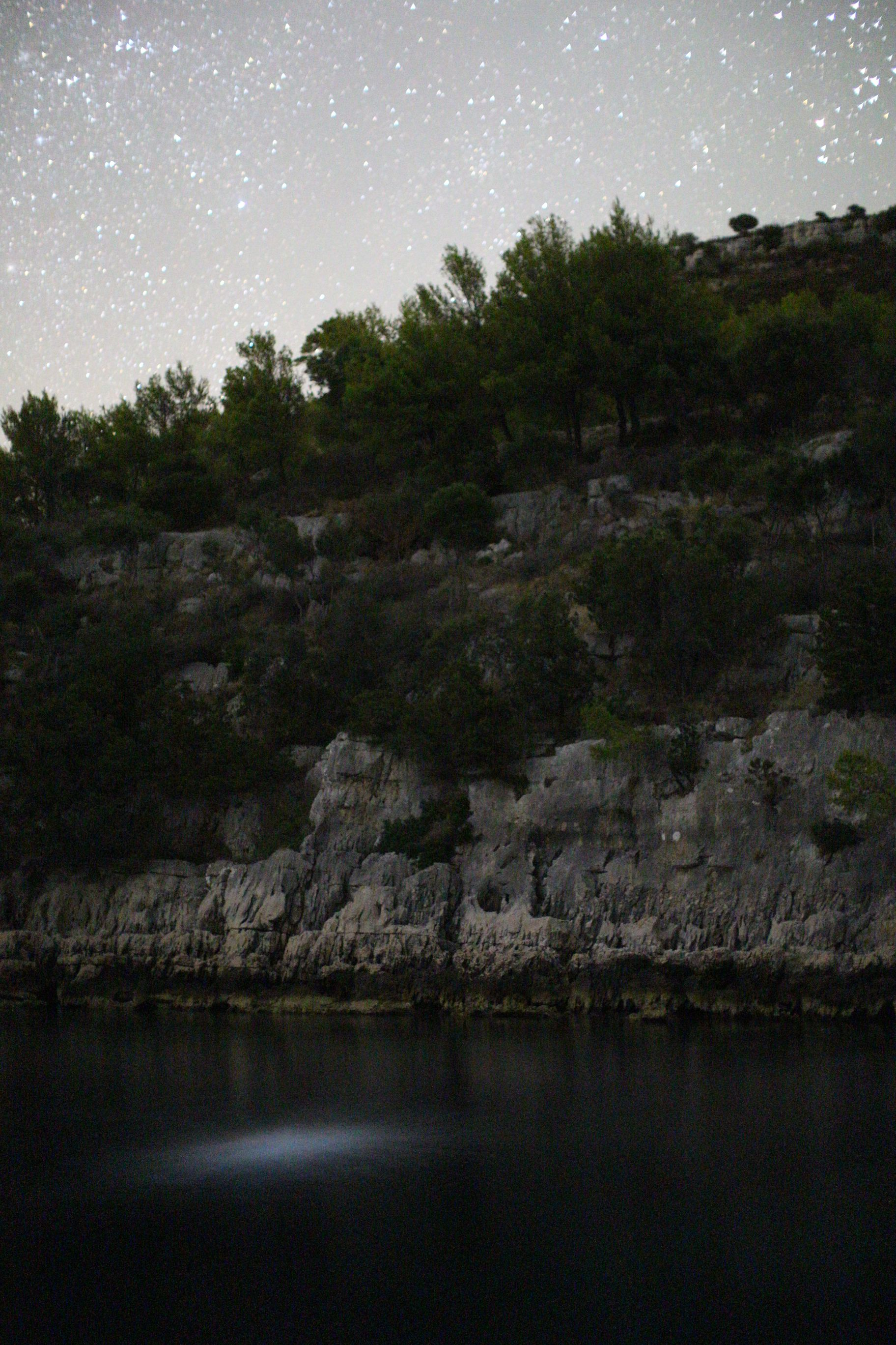 Lastovo, Croatia - stars with bioluminiscent plankton and reflection of stones and stars in water of Skrivena Luka MR